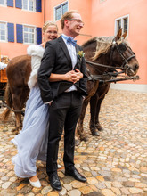 Happy Bride And Groom On Cobblestone Square With Carriage