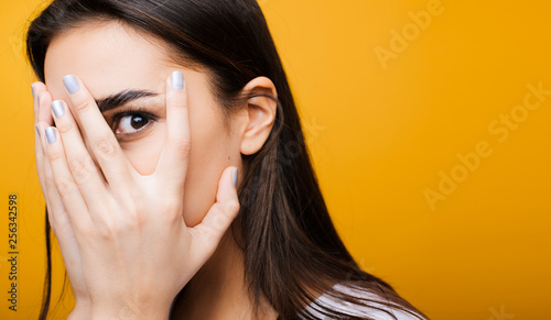 Fotografía  Close up portrait of a cute young european girl hiding face with her hand while looking at camera through fingers in front of a yellow studio background