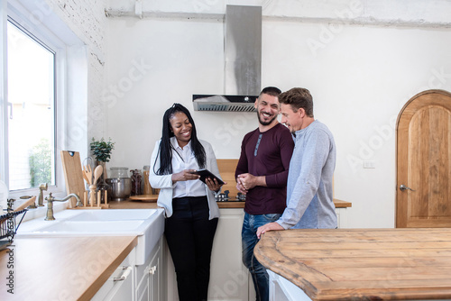 Female real estate agent showing gay couple around new house Wallpaper Mural