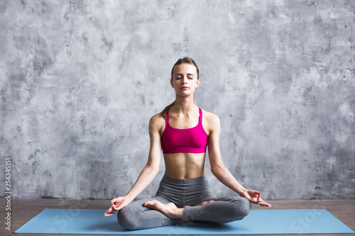 Fit female meditating in lotus pose at home. Woman doing yoga exercise indoors.