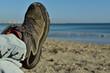 fuß im wanderschuh mit jeans liegt am strand in der sonne am meer