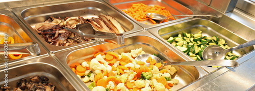 Fototapeta steel trays with plenty of vegetables cooked and raw in the cafe obraz