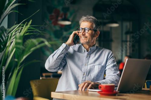 Fototapety, obrazy: happy senior businessman using cellphone in cafeteria on coffee break