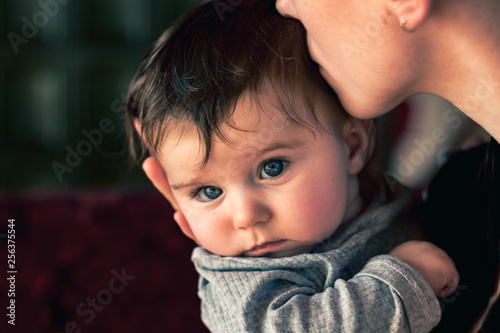 Photo mother kissing her sad baby