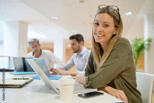 Obraz na plátně Female startup team member smiling at camera in office