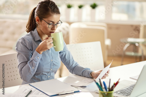 Valokuva  Young businesswoman drinking coffee and going through paperwork in the office