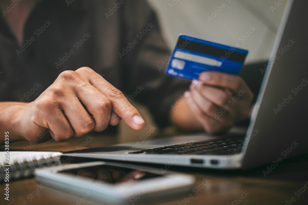 Fototapeta Businessman holding credit card and typing on laptop for online shopping and payment makes a purchase on the Internet, Online payment, Business financial and technology