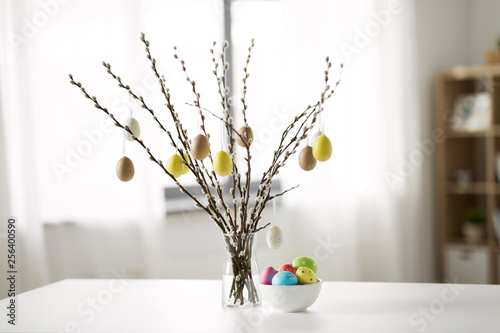 Photo holidays and object concept - pussy willow branches decorated by easter eggs in