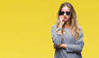 Young beautiful blonde woman wearing sunglasses over isolated background looking stressed and nervous with hands on mouth biting nails. Anxiety problem.