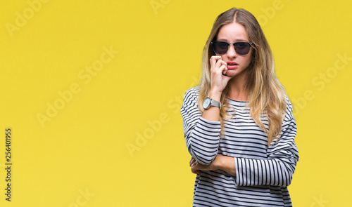 Photo  Young beautiful blonde woman wearing sunglasses over isolated background looking stressed and nervous with hands on mouth biting nails