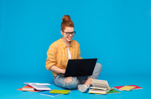 Education, High School, Technology And People Concept - Red Haired Teenage Student Girl In Checkered Shirt And Torn Jeans With Books Using Laptop Computer Over Bright Blue Background
