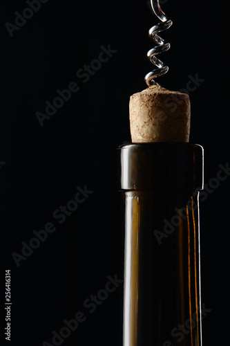 Fotografía  Glass wine bottle with wooden cork and corkscrew isolated on black