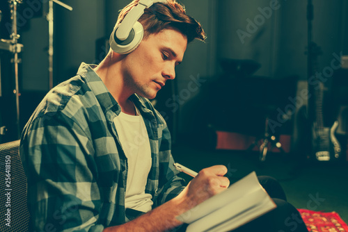 serious young composer listening music in headphones while writing in notebook - 256418150