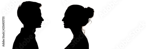 Fotografiet silhouetteof a guy and a girl looking at each other, head profile of teenagers i