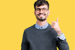 Young handsome smart man wearing glasses over isolated background doing happy thumbs up gesture with hand. Approving expression looking at the camera showing success.