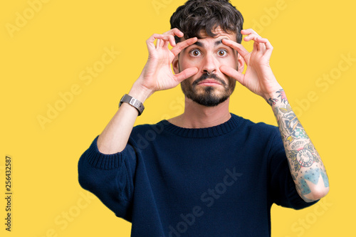 Photo Young handsome man over isolated background Trying to open eyes with fingers, sl