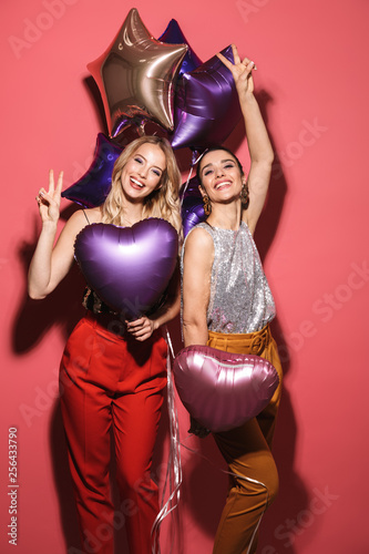 Image of two posh girls 20s in stylish outfit laughing and holding festive ballo фототапет