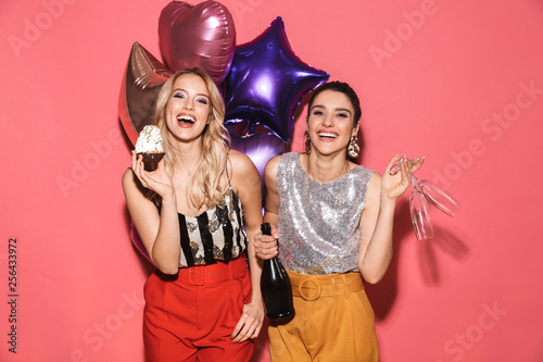 Photo of two adorable women 20s in stylish outfit holding festive balloons and d Wallpaper Mural