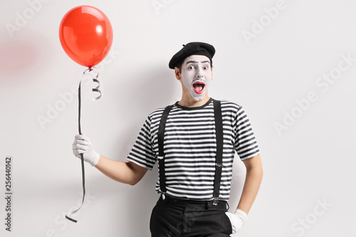 Obraz na plátně  Mime holding a red balloon and leaning against wall