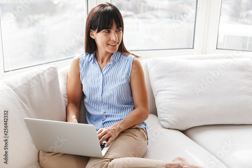 Portrait of mature woman 40s using silver laptop while sitting on couch in brigh Wallpaper Mural