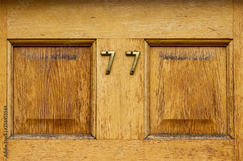Fotografie, Obraz  House number 77 with the seventy seven on a eyllow natural wood door
