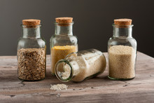 Glass Jars For An Eco Friendly Shopping Or Storage Of Goods, On A Natural Wooden Surface. Ideas For Kitchen Decoration, Presentation. Asorted Rice, Corn Meal, Sesame Seeds And Oats.
