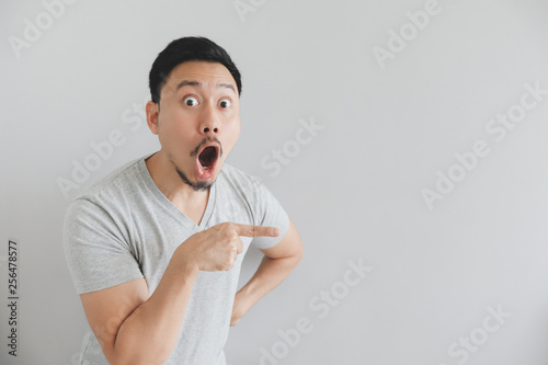 Photographie  Wow and surprised face of man in grey t-shirt with hand point on empty space