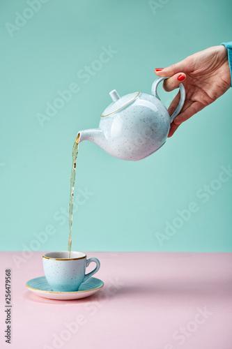 Fototapeta Tea pot pouring tea in a cup on blue backdrop