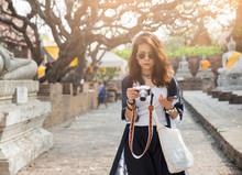 Beautiful Woman Holding Mirrorless,take Photo At Ayutthaya Historical Park,Thailand.