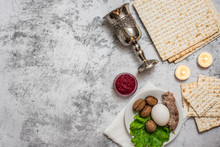 Jewish Holiday Passover Background With Wine, Matza And Seder Plate On Grey. Top View. With Copy Space