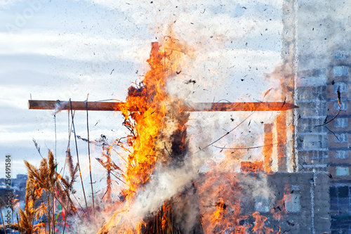 Fotografiet  Burning wooden cross. City. National Slavic and pagan customs