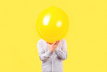 Man Holding Yellow Balloon With Smile Face Emotion Instead Of Head. Positive Thinking Concepts, Image On A Yellow Background