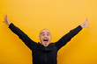 A young bald man joyously throws his hands up in the air. isolated yellow background, black shirt, copy space