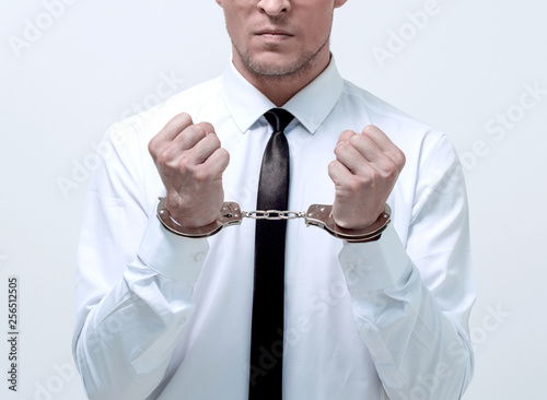 Leinwand Poster young businessman in handcuffs.
