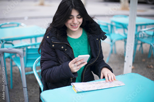 Foto  Young woman tourist sitting in a cafe outdoors, using smartphone, holding destin