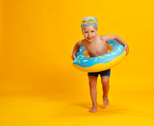Happy Child Boy In Swimsuit With Swimming Ring Donut On Colored Yellow Background.