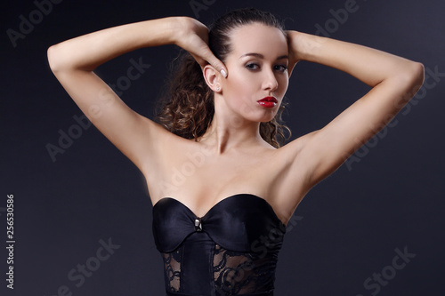 Photographie Portrait of beautiful young girl in a silk black dress with lace corsage on dark background