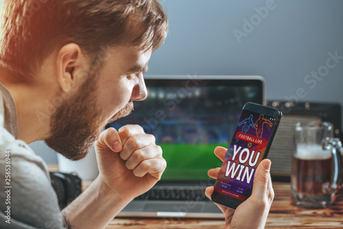 Slika na platnu Man celebrating victory after making bets at bookmaker website