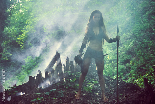 Fotomural  Beautiful amazon girl in metal mail with a spear in a misty forest
