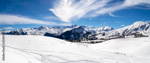 Obraz Panoramic landscape with mountain peaks in the French Alps, above La Toussuire village, on a sunny Winter day, in Les Sybelles ski area. - fototapety do salonu