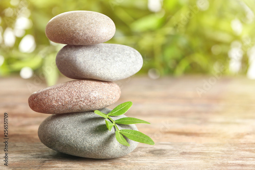 Foto op Plexiglas Spa Spa stones and bamboo leaves on table against blurred background. Space for text