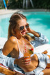 beautiful woman with long hair in sunglasses. Female on vacation spends time by the pool with a cocktail