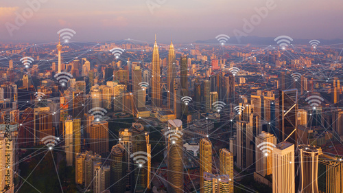 Canvas Prints Kuala Lumpur Digital network connection lines and wifi icons with Kuala Lumpur Downtown, Malaysia. Financial district in smart city in technology concept. Skyscraper and high-rise buildings at sunset