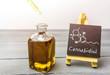 Leinwanddruck Bild - Cbd oil in glass bottle and chalkboard with molecule drawing on table