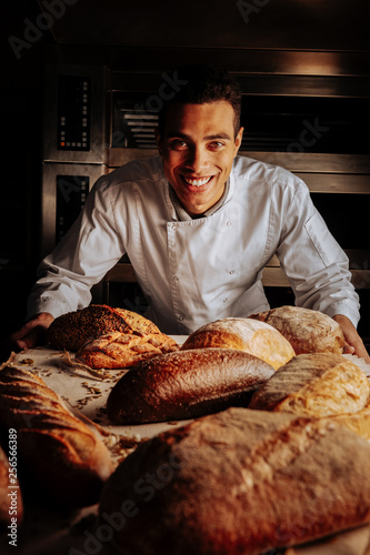 Fotografia Baker smiling broadly standing near table with bread