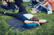 Man At An Outdoor Concert Resting Lying On A Green Lawn