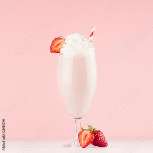 Foto op Plexiglas Milkshake Sweety dairy yogurt of ripe strawberry with whipped cream and straw, slices juicy berry on soft light pink background.