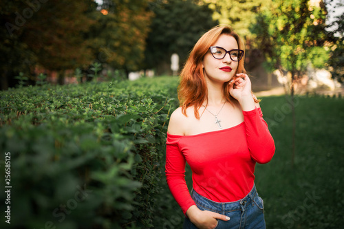 Fotografía  Attractive redhaired woman in eyeglasses, wear on red blouse and jeans skirt posing at green park
