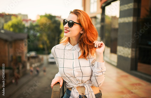 Attractive redhaired woman in sunglasses, wear on white blouse posing at street against modern building.