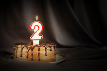 Two Years Anniversary. Birthday Chocolate Cake With White Burning Candle In The Form Of Number Two. Dark Background With Black Cloth